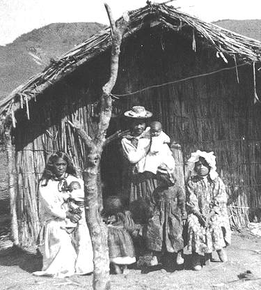 Maori family pose outside their whare